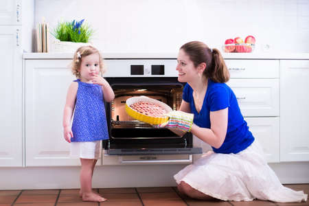 Mother and child bake a pie. Young woman and her daughter cook in a white kitchen. Kids baking pastry. Children helping to make dinner. Modern interior with oven and other appliances. Family eating. photo