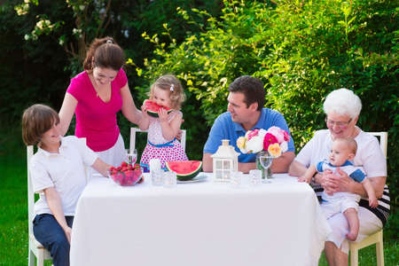 family outside: Big family with children have lunch outdoors. Parents with 3 kids and grandmother eat in the garden. Picnic for mother father baby boy toddler girl and teenager child. Generations and retirement.