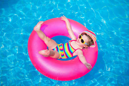 Child in swimming pool. Little girl playing in water. Vacation and traveling with kids. Children play outdoors in summer. Kid with inflatable ring toy. Swim wear and sun glasses for UV protection. Archivio Fotografico