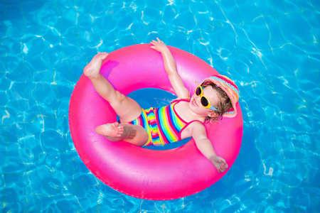 ao ar livre: Criança na piscina. Menina que joga na água. Férias e viajando com crianças. As crianças brincam ao ar livre no verão. Criança com brinquedo anel inflável. Desgaste e óculos de sol de natação para proteção UV.