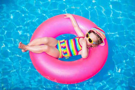 persona feliz: Ni�o en piscina. Ni�a que juega en el agua. Vacaciones y viajar con ni�os. Los ni�os juegan al aire libre en verano. Ni�os con el juguete inflable anillo. Desgaste y el sol de nataci�n gafas de protecci�n UV. Foto de archivo