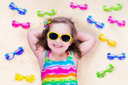 child protection: Child wearing sunglasses on a beach. Sun eye wear for kids. Little girl choosing spectacles. Lens and colorful frame choice for children. UV protection for kids. Safe glasses for tropical vacation.