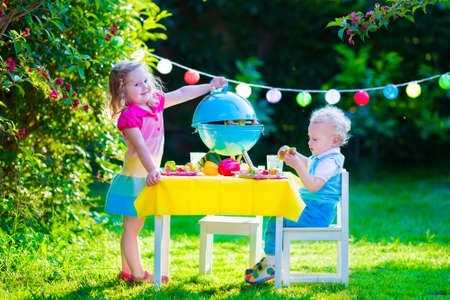 meat grill: Children grilling meat. Family camping and enjoying BBQ. Brother and sister at barbecue preparing steaks and sausages. Kids eating grill and healthy vegetable meal outdoors. Garden party for child. Stock Photo