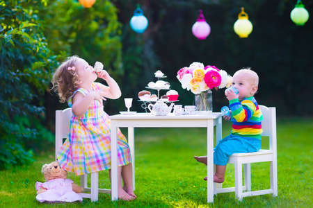 for tea: Garden birthday party for children. Kids outdoor celebration. Little boy and girl drinking tea and eating cake playing in the backyard in summer. Toddler and baby play with toy dishes and eat cupcakes Stock Photo