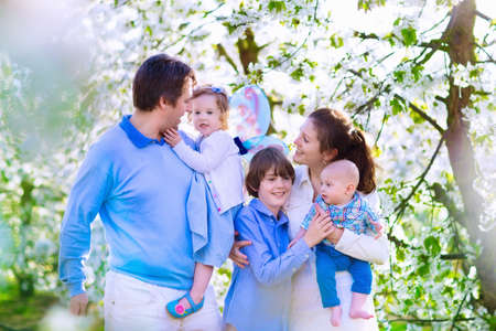 Family with kids in a blooming spring garden. Parents with three children baby toddler girl and boy enjoying picnic on a farm with apple and cherry trees. Mother father son and daughter in summer photo