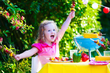 corn meal: Children grilling meat. Family camping and enjoying BBQ. Little girl at barbecue preparing steaks kebab and corn. Kids eating grill and healthy vegetable meal outdoors. Garden party for toddler child
