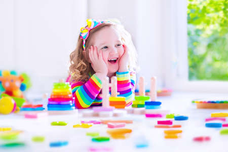Preschooler child playing with colorful toy blocks. Kids play with educational wooden toys at kindergarten or day care. Preschool children build tower with wood block. Toddler kid in nursery. Stock Photo