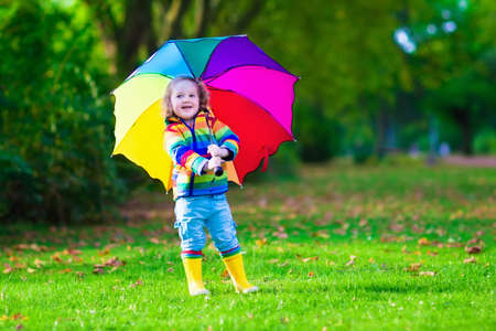 Child with colorful umbrella playing in the rain. Kids play outdoors by rainy weather. Toddler kid in coat and waterproof boots jumping in autumn garden. Fall fun for children raining in the park. photo