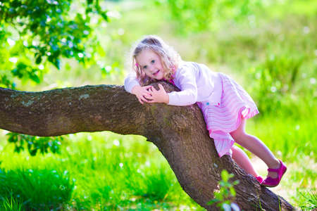 Little girl hiking in a forest. Outdoor fun for family in country side. Summer hike with young children. Toddler kid playing in a park climbing a tree. Child running in the woods. Kids and climb. photo