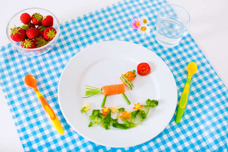 corn meal: Healthy vegetarian lunch for little kids. Kid meal. Vegetable and fruit served as animals corn broccoli carrot strawberry helping child to learn eating right and clean children hands with spoon Stock Photo