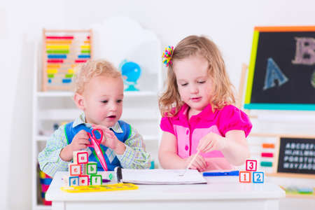 Děti v mateřské školce. Dvě děti kreslení a malování v mateřské škole. Chlapec a dívka šťastný jít zpátky do školy. Batole dítě a dítě učit písmena na péči o dítě. Třída pokoj s tabuli a počítadlem