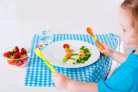 manos limpias: Comida vegetariana saludable para los niños pequeños. Comida Kid. Hortalizas y frutas sirven como animales de brócoli maíz fresa zanahoria ayuda a los niños a aprender comiendo manos derechas y niños limpios con la cuchara Foto de archivo