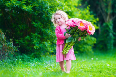 Little cute girl with peony flowers. Child wearing a pink dress playing in a summer garden. Kids gardening. Children play outdoors. Toddler kid with flower bouquet for birthday or mothers day.