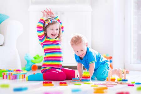 vzdělávací: Předškolák dítě si hraje s barevnými hračkami bloky. Děti hrají s vzdělávacími dřevěných hraček v mateřské škole nebo denní péči. Předškolní děti postavit věž s dřevěným blokem. Batole dítě v dětském pokoji.