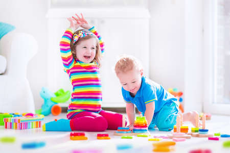 kid's day: Preschooler child playing with colorful toy blocks. Kids play with educational wooden toys at kindergarten or day care. Preschool children build tower with wood block. Toddler kid in nursery. Stock Photo