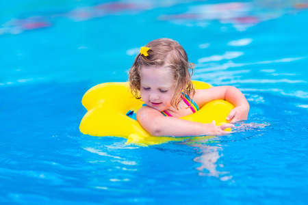 Kids in swimming pool. Children swim outdoors. Toddler child during vacation in a tropical resort with palm trees. Little girl playing on a beach. Active kid in summer with colorful toy floating ring. Stock Photo