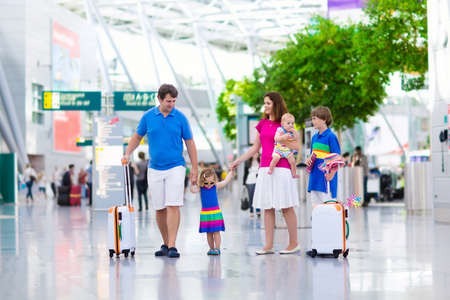 fly: Family traveling with kids. Parents with children at international airport with luggage. Mother and father hold baby toddler girl and boy flying by airplane. Travel with child for summer vacation.