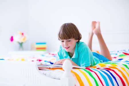 family with one child: School age boy reading a book in bed. Children read books. Kids learning. Student kid doing homework in a sunny bedroom. Colorful textile bedding for child room. Smart students learn and study at home