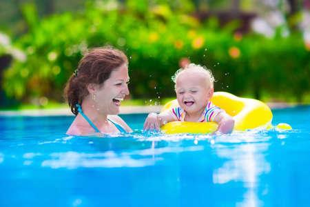 Moeder en baby in zwembad. Ouder en kind zwemmen in een tropisch resort. Zomer outdoor activiteit voor gezin met kinderen. Vakantie en reizen met jonge kinderen. Opblaasbaar speelgoed voor waterpret. Stockfoto