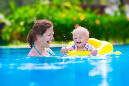 pool water: Mother and baby in swimming pool. Parent and child swim in a tropical resort. Summer outdoor activity for family with kids. Vacation and traveling with young children. Inflatable toys for water fun.