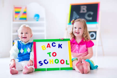 Kids at preschool. Two children drawing and painting at kindergarten. Boy and girl happy to go back to school. Toddler kid and baby learn letters at child care. Class room with chalkboard and abacus photo