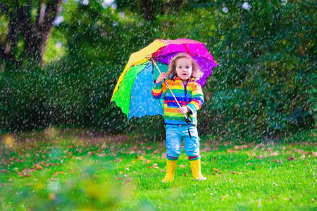 雨の中で遊ぶカラフルな傘の子。子供は雨の天気で屋外プレイします。幼児子供コートで防水ブーツ秋の庭にジャンプします。子供公園で雨の秋楽