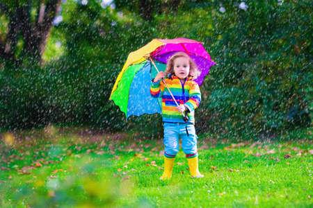 botas de lluvia: Niño con el paraguas de colores que juegan en la lluvia. Los niños juegan al aire libre por el tiempo lluvioso. Niño del niño en botas capa impermeable y saltando en el jardín de otoño. Caída de la diversión para los niños que llueven en el parque.
