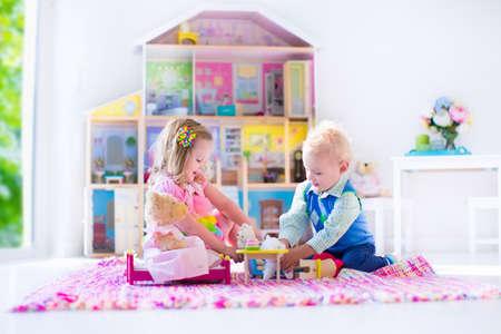 case colorate: Bambini che giocano con casa di bambola e giocattoli animali imbalsamati. I bambini si siedono su un tappeto rosa, in una sala giochi in casa o all'asilo. Bambino bambino e bambino con il giocattolo della peluche e bambole. Festa di compleanno per il bambino.