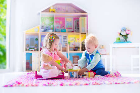 bedrooms: Kids playing with doll house and stuffed animal toys. Children sit on a pink rug in a play room at home or kindergarten. Toddler kid and baby with plush toy and dolls. Birthday party for little child. Stock Photo
