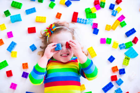 Preschooler child playing with colorful toy blocks. Kids play with educational toys at kindergarten or day care. Preschool children build tower with plastic block. Toddler kid in nursery. photo