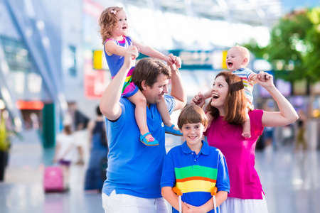 baggage: Family traveling with kids. Parents with children at international airport with luggage. Mother and father hold baby toddler girl and boy flying by airplane. Travel with child for summer vacation.