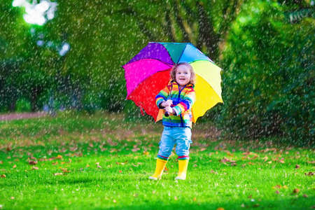Child with colorful umbrella playing in the rain. Kids play outdoors by rainy weather. Toddler kid in coat and waterproof boots jumping in autumn garden. Fall fun for children raining in the park.