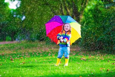 Kind met kleurrijke paraplu spelen in de regen. Kinderen spelen buiten bij regenachtig weer. Peuter kind in jas en waterdichte laarzen springen in de herfst tuin. Fall leuk voor kinderen regenen in het park.