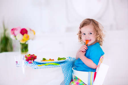having lunch: Child having vegetables for lunch. Healthy fruit and vegetable meal for children. Kids eat in a white dining room or kitchen. Toddler kid having breakfast. Food for preschooler at home or daycare.