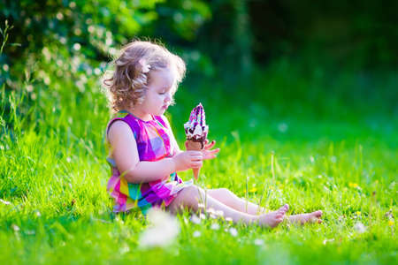 Child eating ice cream. Kids play outdoors enjoying sweet snack on a hot summer day. Children eat icecream. Toddler kid playing in the garden. Little girl with vanilla and chocolate ice cone.