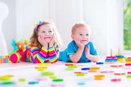 preescolar: Preescolar niño jugando con bloques de juguete de colores. Los niños juegan con los juguetes de madera educativos en jardín de infantes o guardería. Los niños de preescolar construir la torre con el bloque de madera. Niño del niño en la guardería.