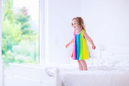 summer dress: Children jump on a bed. Cute little girl jumping and dancing in a sunny white bedroom. Kids room with garden view window. Toddler kid on a summer morning. Bedding and textile for baby and child. Stock Photo