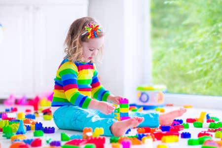 preescolar: Preescolar ni�o jugando con bloques de juguete de colores. Los ni�os juegan con los juguetes educativos en el jard�n de infantes o guarder�a. Los ni�os de preescolar construir la torre con bloques de pl�stico. Ni�o del ni�o en la guarder�a. Foto de archivo