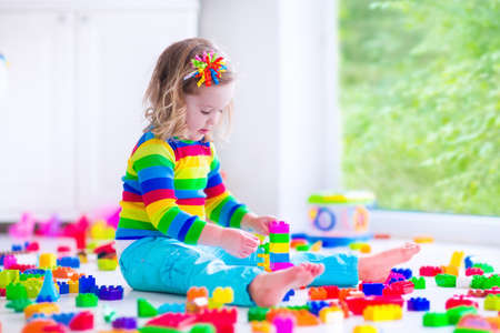 day care: Preschooler child playing with colorful toy blocks. Kids play with educational toys at kindergarten or day care. Preschool children build tower with plastic block. Toddler kid in nursery.