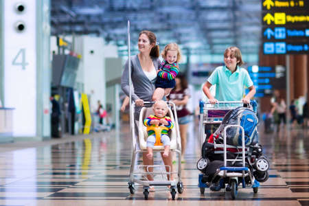 boarding: Family traveling with kids. Parents with children at international airport with luggage in a cart. Mother holding baby toddler girl and boy flying by airplane. Travel with child for summer vacation.