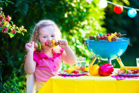 kebab: Children grilling meat. Family camping and enjoying BBQ. Little girl at barbecue preparing steaks kebab and corn. Kids eating grill and healthy vegetable meal outdoors. Garden party for toddler child