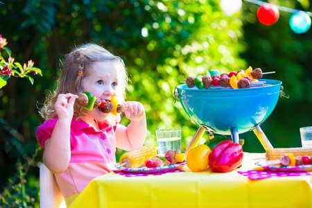 Kinderen grillen van vlees. Familie camping en genieten van BBQ. Meisje bij barbecue voorbereiding steaks kebab en maïs. Kinderen eten grill en gezonde groente maaltijd buitenshuis. Tuinfeest voor peuter kind