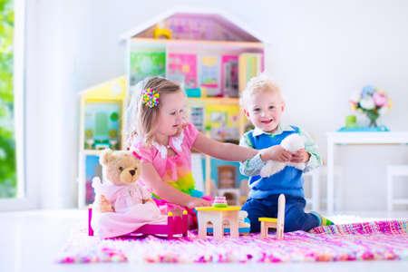 人形の家と動物のぬいぐるみと遊ぶ子供たち。自宅の遊戯室や幼稚園でピンクの敷物の上に子供が座っています。幼児子供とぬいぐるみと人形の赤