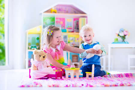 baby doll: Kids playing with doll house and stuffed animal toys. Children sit on a pink rug in a play room at home or kindergarten. Toddler kid and baby with plush toy and dolls. Birthday party for little child. Stock Photo