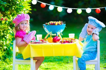 子供たちは肉を焼きます。家族キャンプやバーベキューを楽しみます。兄と妹バーベキュー ステーキやソーセージの準備で。グリルおよび屋外で野
