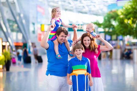 viaje familia: Familia que viaja con niños. Los padres con hijos en el aeropuerto internacional con el equipaje. La madre y el padre tienen bebé niño niña y un niño volar en avión. Viajar con niños para las vacaciones de verano.