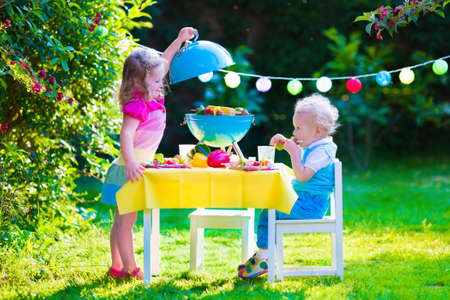 Children grilling meat. Family camping and enjoying BBQ. Brother and sister at barbecue preparing steaks and sausages. Kids eating grill and healthy vegetable meal outdoors. Garden party for child. Stockfoto