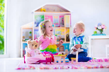 Kids playing with doll house and stuffed animal toys. Children sit on a pink rug in a play room at home or kindergarten. Toddler kid and baby with plush toy and dolls. Birthday party for little child. Stock Photo