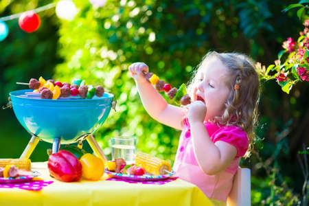barbecue: Children grilling meat. Family camping and enjoying BBQ. Little girl at barbecue preparing steaks kebab and corn. Kids eating grill and healthy vegetable meal outdoors. Garden party for toddler child