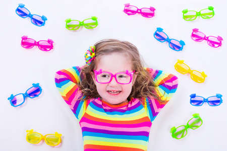 specs: Child wearing eye glasses. Eye wear for kids. Little girl choosing spectacles. Lens and colorful frame choice for children. Vision and sight control at optician shop. Smart preschooler with eyeglasses Stock Photo